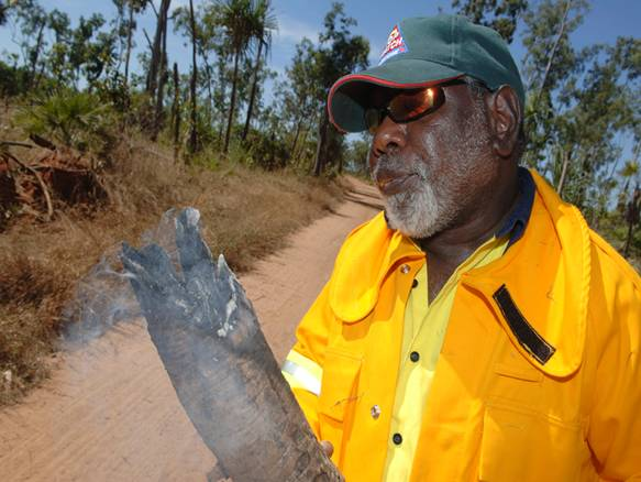 A resident of the Tiwi Islands holds a smoking piece of wood.